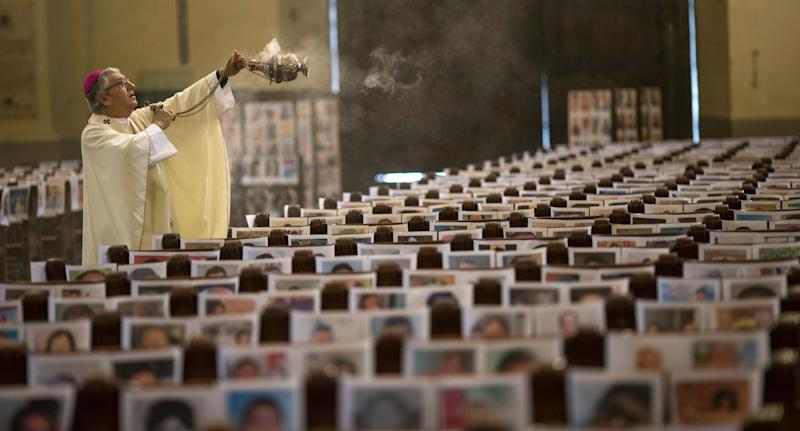 The Archbishop of Lima Carlos Castillo swings a censer over thousands of portraits of COVID-19 victims. Source: AAP