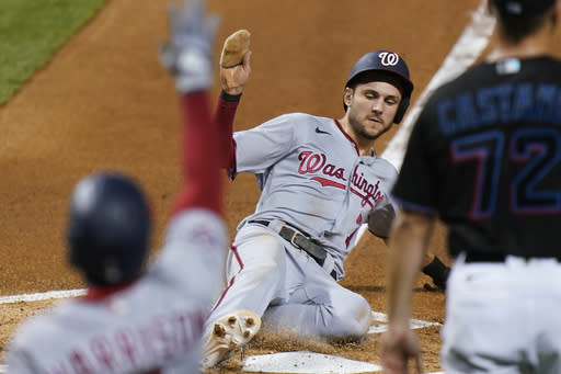 Washington Nationals' Trea Turner slides into home to score on a sacrifice fly by Kurt Suzuki during the first inning of the second game of the team's baseball doubleheader against the Miami Marlins, Friday, Sept. 18, 2020, in Miami. (AP Photo/Wilfredo Lee)