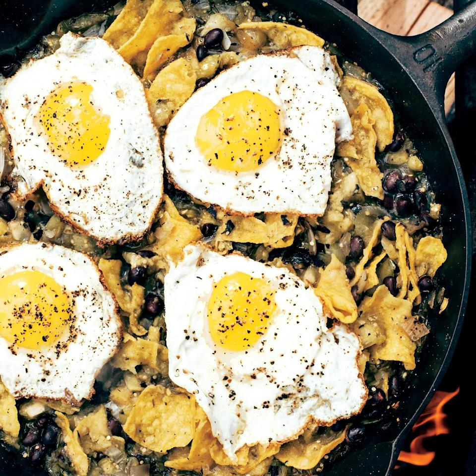 """Toss tortilla chips with a grilled-tomatillo salsa and black beans, then top with cast-iron fried eggs for vibrant breakfast you can eat by the campfire or in your backyard. <a href=""""https://www.epicurious.com/recipes/food/views/chilaquiles-with-blistered-tomatillo-salsa-and-eggs-56389733?mbid=synd_yahoo_rss"""" rel=""""nofollow noopener"""" target=""""_blank"""" data-ylk=""""slk:See recipe."""" class=""""link rapid-noclick-resp"""">See recipe.</a>"""