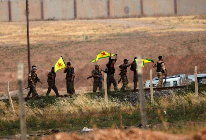 Kurdish People's Protection Units fighters hold their movement's flag near the Akcakale crossing gate between Turkey and Syria on June 15, 2015 (AFP Photo/Bulent Kilic)