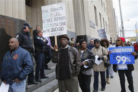 City of Detroit Public Works pensioner Ernest Thomas (C), 79, carries a sign as he protests cuts in city worker pensions in front of the Federal Court House in Detroit, Michigan October 28, 2013. REUTERS/Rebecca Cook