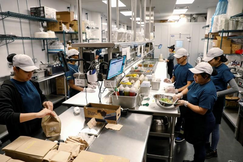Workers prepare orders in the kitchen at the newest Chopt Creative Salad Co., location in New York