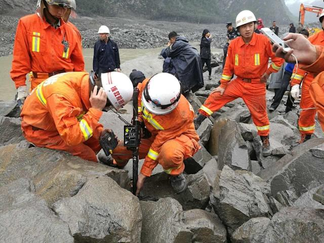 <p>Rescuers work at the accident site after a landslide at Xinmo Village of Maoxian County on June 24, 2017 in Tibetan and Qiang Autonomous Prefecture, Sichuan Province of China. (Photo: VCG/VCG via Getty Images) </p>