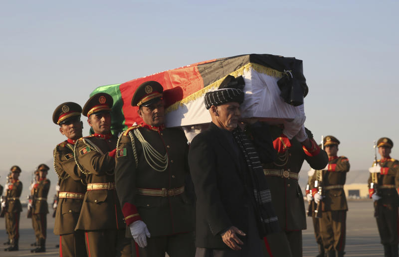 Afghan President Ashraf Ghani, foreground, and Afghan honor guards carry the coffin of Japanese physician Tetsu Nakamura during a ceremony before transporting his body to his homeland, at the Hamid Karzai International Airport in Kabul, Afghanistan, Saturday, Dec. 7, 2019. Nakamura was killed earlier this week in a roadside shooting in eastern Afghanistan. (AP Photo/Rahmat Gul)
