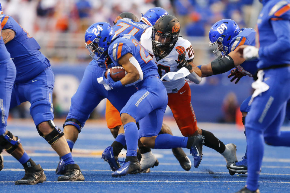 Boise State running back George Holani (24) is stopped by Oklahoma State linebacker Malcolm Rodriguez (20) during the first half of an NCAA college football game Saturday, Sept. 18, 2021, in Boise, Idaho. (AP Photo/Steve Conner)