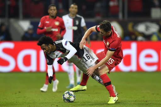 Juventus' Juan Cuadrado, left, is tackled by Leverkusen's Julian Baumgartlinger during the Champions League Group D soccer match between Bayer Leverkusen and Juventus at the BayArena in Leverkusen, Germany, Wednesday, Dec. 11, 2019. (AP Photo/Martin Meissner)