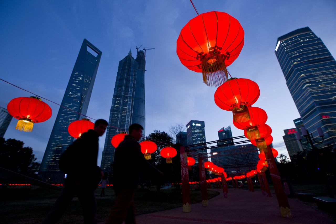 Pedestrians walk under red lanterns which was recently installed as Chinese New Year decorations, at Pudong Financial Area in Shanghai