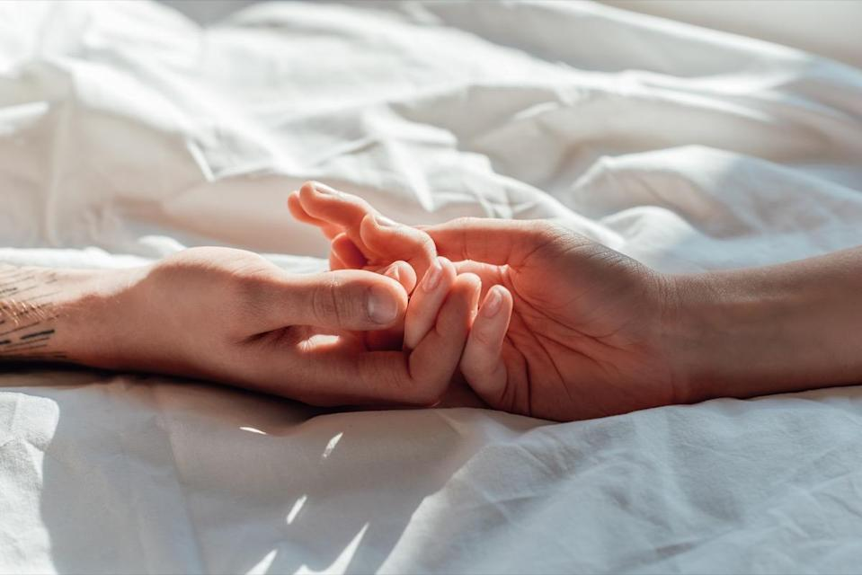 couple in live holding hads while lying in bed together