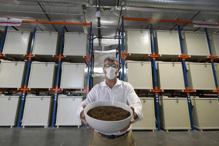 Micah Truman, CEO of Return Home, a company that composts human remains into soil, poses for a photo, Wednesday, Sept. 15, 2021, in Auburn, Wash., south of Seattle. Truman is holding a container of soil made with animal remains that is used to show what the product of their process looks like. Behind him are the metal vessels where bodies are kept during the first month of the two-month composing process. Earlier in September, Colorado became the second state after Washington to allow human body composting, and Oregon will allow the practice beginning next July. (AP Photo/Ted S. Warren)