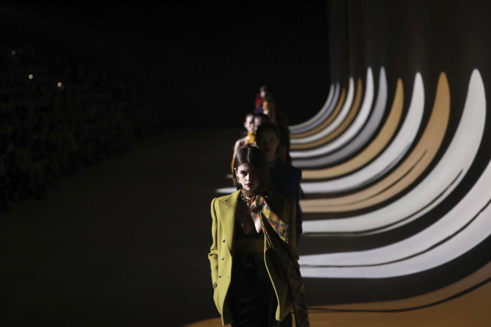 FILE - In this Feb.25, 2020 file photo, model Kaia Gerber leads other models as they wear creations for the Saint Laurent fashion collection during Women's fashion week Fall/Winter 2020/21 presented in Paris. Gucci and St. Laurent are two of the highest profile fashion houses to announce they will leave the fashion calendar behind, with its relentless four-times a year rhythm, shuttling cadres of fashionistas to global capitals where they squeeze shoulder-to-shoulder around runways for 15 breathless minutes. The coronavirus lockdown -- which has hit luxury fashion houses on their bottom lines -- has also given pause to rethink the pace of fashion. (Photo by Vianney Le Caer/Invision/AP, File)