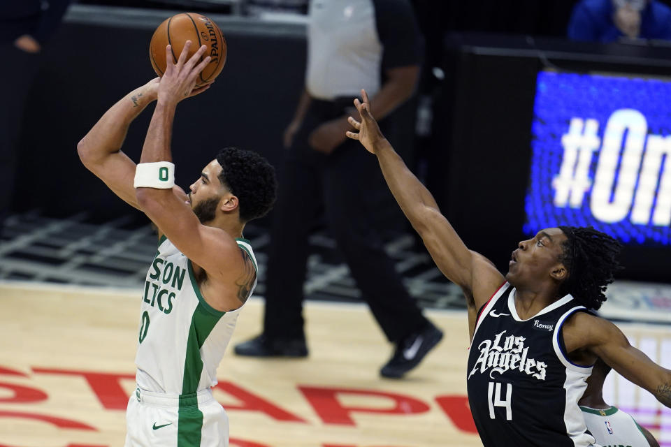 Boston Celtics forward Jayson Tatum, left, shoots next to Los Angeles Clippers guard Terance Mann (14) during the first half of an NBA basketball game Friday, Feb. 5, 2021, in Los Angeles. (AP Photo/Marcio Jose Sanchez)