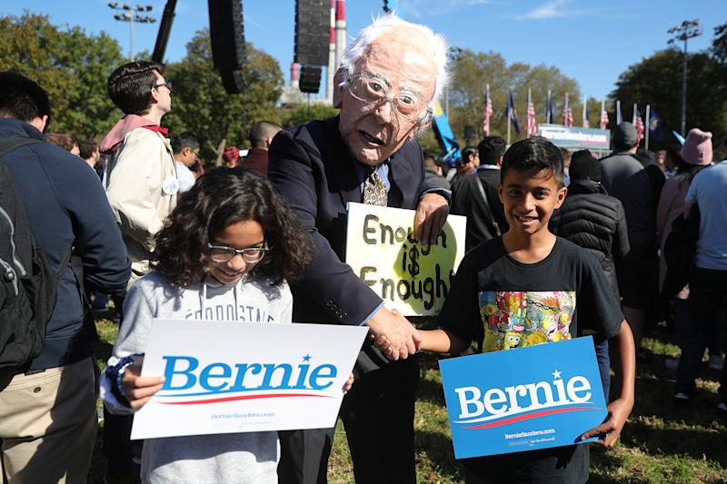 A man wearing a mask of Democratic presidential candidate Sen. Bernie Sanders, I-Vt., poses with people as they attend a campaign rally in Long Island City, N.Y., Oct. 19, 2019. (Photo: Gordon Donovan/Yahoo News)