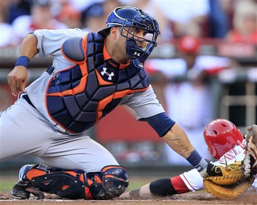 Cincinnati Reds' Zack Cozart, right, is safe at home ahead of the tag by Detroit Tigers catcher Gerald Laird in the first inning of a baseball game, Friday, June 8, 2012, in Cincinnati. (AP Photo/Al Behrman)
