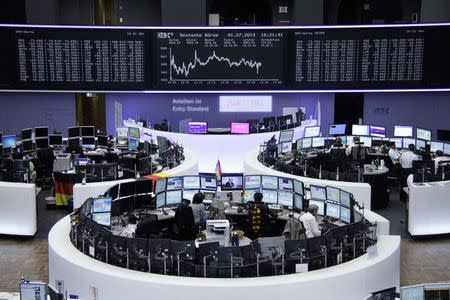 Traders are pictured at their desks in front of DAX board at the Frankfurt stock exchange