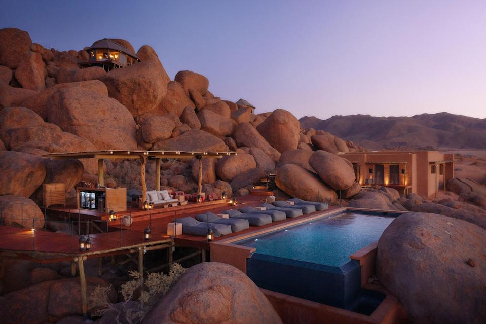 """<p><strong>Why did this hotel catch your attention? What's the vibe?</strong> Sonop caught my attention by being nearly invisible. The tents blend almost perfectly into the massive pile of boulders on which they're constructed, so after driving for five hours through the desert, I felt like I was just looking at more desert. I like the humility in not needing to make the hotel special from the outside, just the inside. You're first met at a reception outbuilding and then driven in a Land Rover to the boulder pile, transferred to an electric golf cart, and driven up a steep, winding path to a welcome area strewn with rugs, overlooking the vast desert.</p> <p><strong>What's the backstory?</strong> Sonop is the fifth hotel opened by Zannier Hotels, their second in Namibia after <a href=""""https://www.cntraveler.com/hotels/namibian-plains/omaanda?mbid=synd_yahoo_rss"""" rel=""""nofollow noopener"""" target=""""_blank"""" data-ylk=""""slk:Omaanda"""" class=""""link rapid-noclick-resp"""">Omaanda</a>. A sixth hotel, in Vietnam, was slated to open this summer. Zannier Hotels is owned by Arnaud Zannier, who's the scion of a French business family known mostly for apparel and vineyards. All the Zannier hotels are decorated by Geraldine Dohogne. Angelina Jolie was the first guest at the Zannier resort in Cambodia, <a href=""""https://www.cntraveler.com/hotels/siem-reap/phum-baitang?mbid=synd_yahoo_rss"""" rel=""""nofollow noopener"""" target=""""_blank"""" data-ylk=""""slk:Phum Baitang"""" class=""""link rapid-noclick-resp"""">Phum Baitang</a>, when she and her family took it over for five months, and she suggested to Arnaud that he visit Namibia. So, she's indirectly responsible for the existence of Sonop.</p> <p><strong>Tell us all about the accommodations. Any tips on what to book?</strong> My room was a very large canvas tent with large mesh windows overlooking the desert. It was decorated in a distinctly colonial style—there was an actual pith helmet, among other antiques—that read as warm and luxurious. The bathroom had a beaut"""