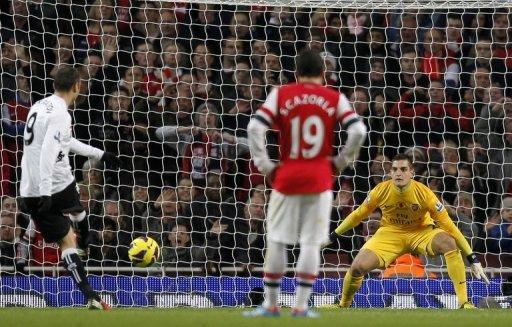Fulham's Bulgarian player Dimitar Berbatov (L) scores his penalty beating Arsenal's Italian goalkeeper Vito Mannone (R) during an English Premier League football match between Arsenal and Fulham at the Emirates Stadium in London. The match ended in a 3-3 draw