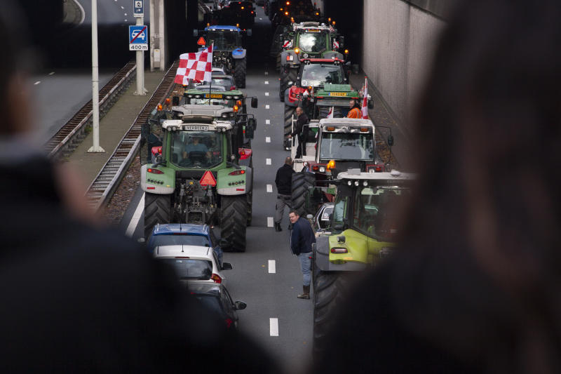 Protesting farmers block a main road leading to the center of The Hague, Netherlands, Wednesday, Oct. 16, 2019. Thousands of Dutch farmers protest over the Netherlands efforts to drastically reduce emissions of greenhouse gases. Among the farmers' demands are that the government does not further reduce the number of animals they can keep. (AP Photo/Peter Dejong)