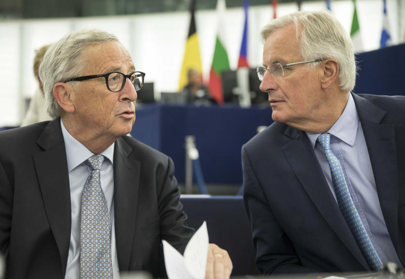 """European Commission president Jean-Claude Juncker, left, speaks whith European Union chief Brexit negotiator Michel Barnier Wednesday, Sept. 18, 2019 at the European Parliament in Strasbourg, eastern France. The risk of Britain leaving the European Union without a divorce deal remains """"very real,"""" European Commission chief Jean-Claude Juncker declared as EU lawmakers debated the ramifications of a no-deal Brexit. (AP Photo/Jean-Francois Badias)"""