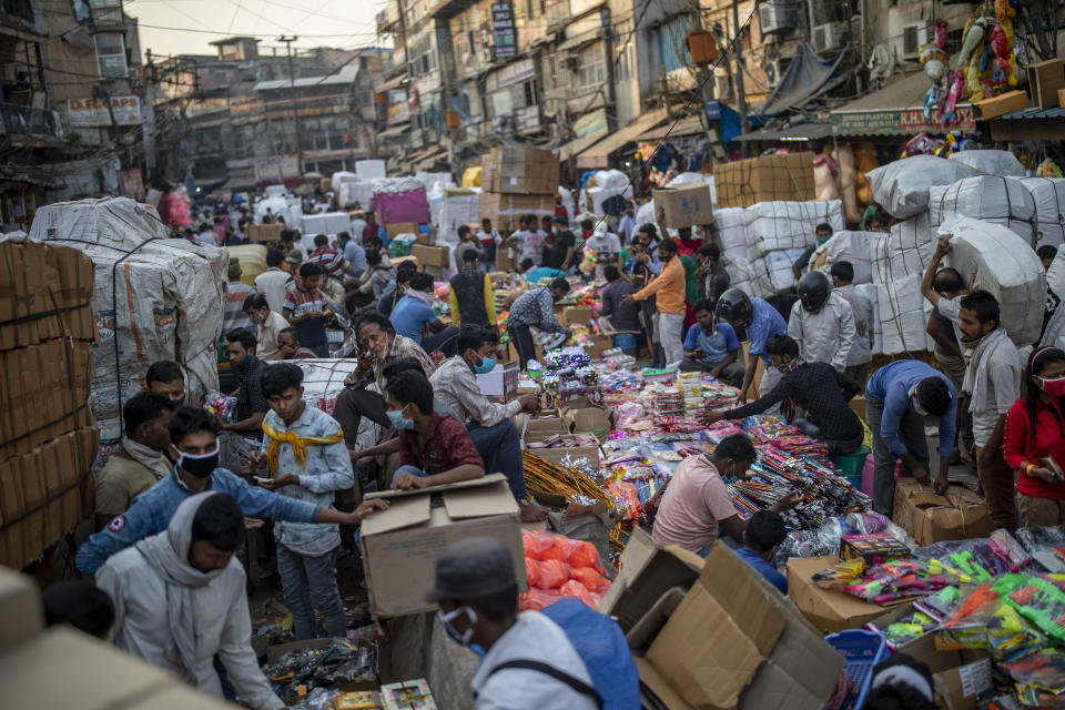 Indians crowd a wholesale market ahead of the Hindu festival of Dussehra in New Delhi, India, Saturday, Oct. 24, 2020. Just weeks after the country of 1.4 billion people fully opened up with a far greater semblance of normality and managed to modestly turn a corner by cutting the new infections by near half, a virus that has killed more than 118,000 Indians and sickened nearly 8 million is expected to return with a renewed surge. The reason: a Hindu festival season that draws tens and thousands of people, packed together shoulder-to-shoulder in temples, shopping districts and congregations, leading to fears and a sense of foreboding among health experts who warn of a whole new cascade of infections, further testing India's already battered healthcare system. (AP Photo/Altaf Qadri)
