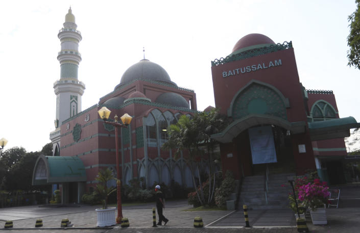 A man walks near an empty mosque in Jakarta, Indonesia, Tuesday, July, 20, 2021. Muslims across Indonesia marked a grim Eid al-Adha festival for a second year Tuesday as the country struggles to cope with a devastating new wave of coronavirus cases and the government has banned large gatherings and toughened travel restrictions. (AP Photo/Achmad Ibrahim)