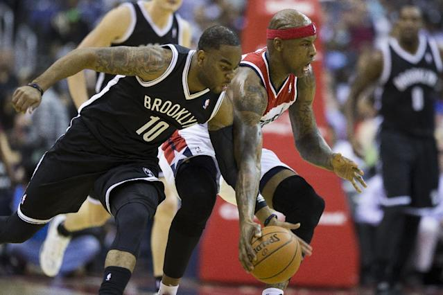 Brooklyn Nets guard Marcus Thornton (10) fights Washington Wizards forward Al Harrington for a loose ball during the first half of an NBA basketball game on Saturday, March 15, 2014, in Washington. (AP Photo/ Evan Vucci)