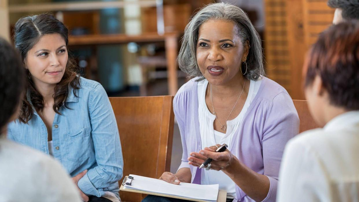 Serious senior African American female mental health profession gestures while talking with clients in a support group or group therapy session.