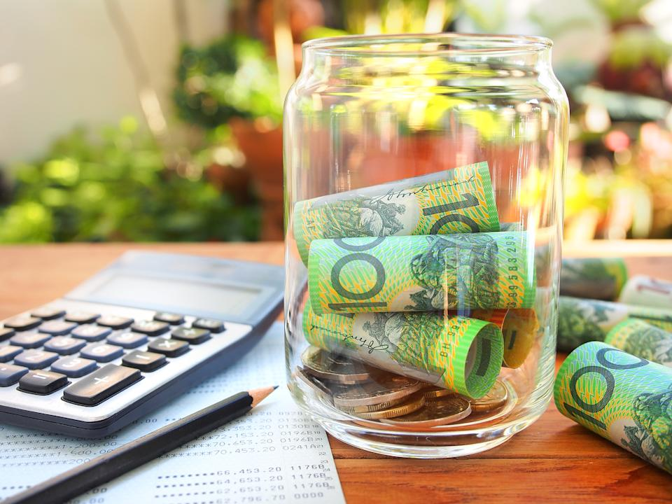 Image of Australian money in a jar, on a table with calculator and pencil