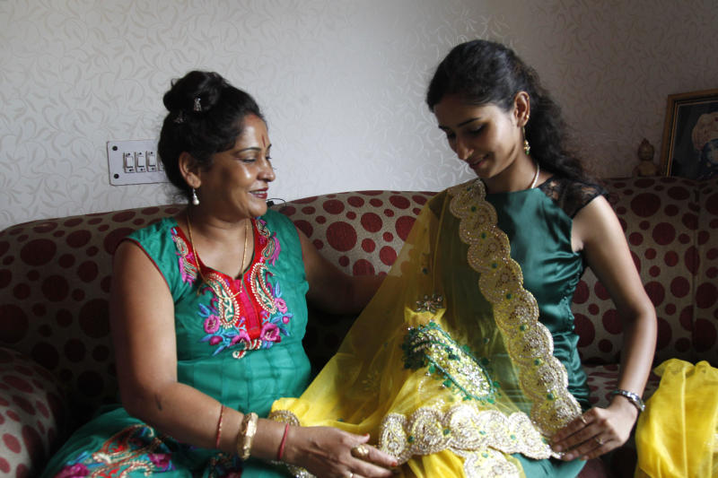 In this Aug 1, 2013 photo, Shagun TV participant Nidhi Gaur, right, shows her mother a traditional Indian dress that she intends to wear at her wedding in New Delhi, India. Indians are obsessed with weddings and obsessed with reality television. Now Shagun TV, a new television channel headquartered in a sprawling suburb of India's capital, is hoping it has found a can't-miss idea — merging the two into a 24-hour matrimonial TV station.(AP Photo/ Shivan Sarna )