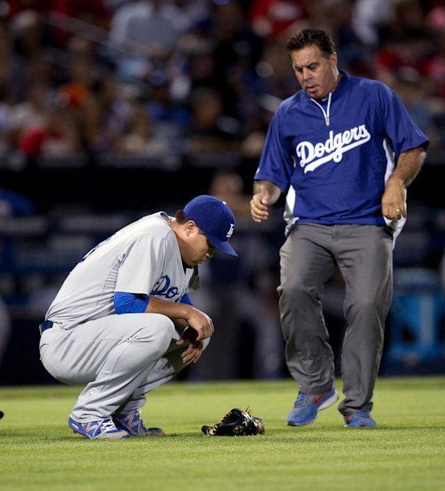 A member of the Los Angeles Dodgers training staff runs onto the field to help injured starting pitcher Hyun-Jin Ryu (99) in the sixth inning of a baseball game against the Atlanta Braves Wednesday, Aug. 13, 2014, in Atlanta. Ryu left the game under his own power. (AP Photo/John Bazemore)