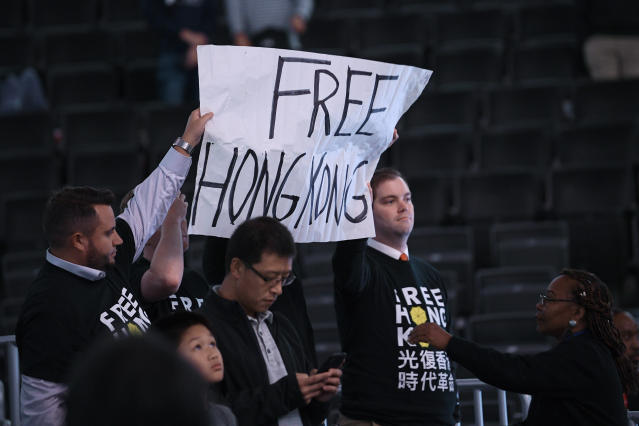 Activists hold up a sign before an NBA exhibition basketball game between the Washington Wizards and the Guangzhou Loong-Lions, Wednesday, Oct. 9, 2019, in Washington. (AP Photo/Nick Wass)