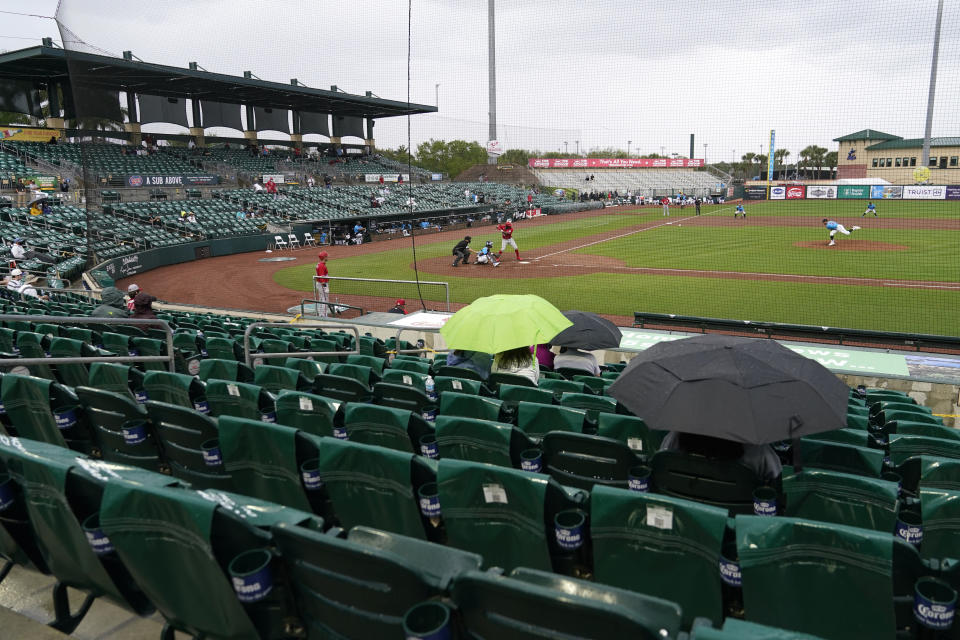 Fans sit in the rain at Roger Dean Stadium during a spring training baseball game between the Miami Marlins and Washington Nationals, Saturday, March 6, 2021, in Jupiter, Fla. (AP Photo/Lynne Sladky)