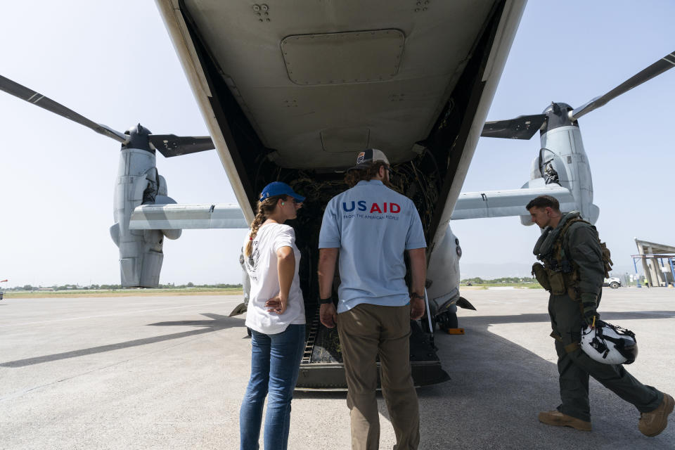 """Aid workers stand after hygiene kits were loaded onto a VM-22 Osprey at Toussaint Louverture International Airport, Saturday, Aug. 28, 2021, in Port-au-Prince, Haiti. The VMM-266, """"Fighting Griffins,"""" from Marine Corps Air Station New River, from Jacksonville, N.C., are flying in support of Joint Task Force Haiti after a 7.2 magnitude earthquake on Aug. 22, caused heavy damage to the country. (AP Photo/Alex Brandon)"""