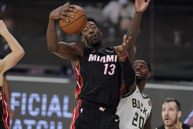 Miami Heat's Bam Adebayo (13) grabs a rebound in front of Milwaukee Bucks' Marvin Williams (20) in the second half of an NBA conference semifinal playoff basketball game Friday, Sept. 4, 2020, in Lake Buena Vista, Fla. (AP Photo/Mark J. Terrill)