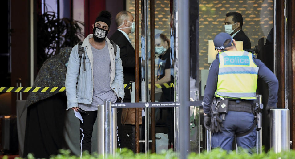 A traveller returned from overseas (L) is escorted from an airport bus into an inner-city hotel in Melbourne.