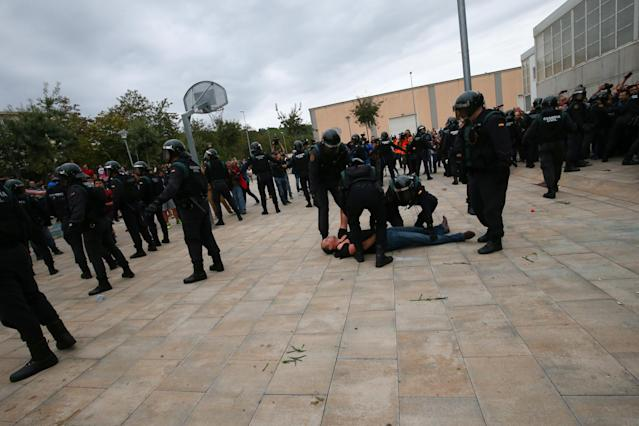 <p>Spanish Civil Guard officers remove a man outside a polling station for the banned independence referendum in Sant Julia de Ramis, Spain on Oct.1, 2017. (Photo: Albert Gea/Reuters) </p>