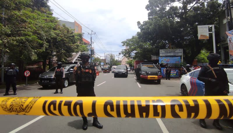Armed police officers stand guard along a closed road following an explosion outside a Catholic church in Makassar, Indonesia