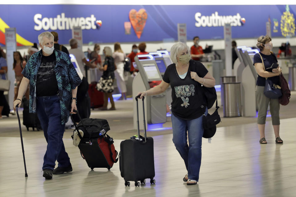 Passengers wearing personal protective face masks walk past the Southwest Airlines ticket counter Tuesday, June 16, 2020, at the Tampa International Airport in Tampa, Fla. Some major US airlines, including United, American Airlines, Delta Air Lines, JetBlue, and Southwest Airlines, pledged to roll out new policies requiring masks for passengers to help stop the spread of the coronavirus. (AP Photo/Chris O'Meara)