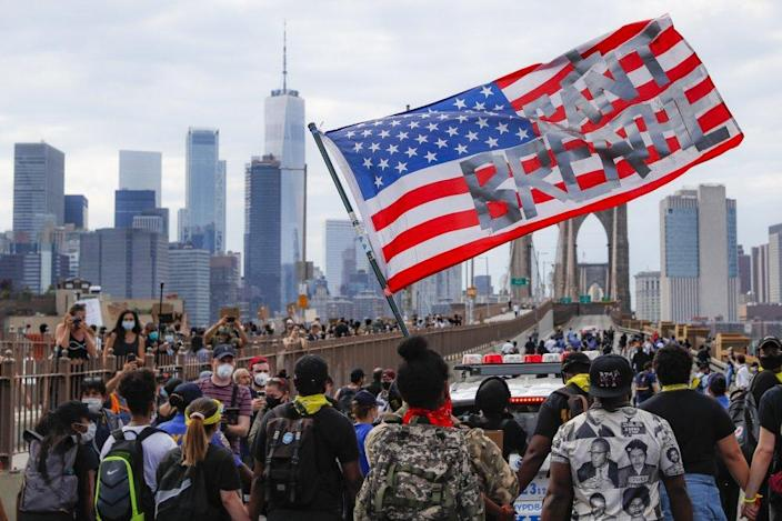 "Protesters march on the Brooklyn Bridge, Thursday, June 4, 2020, in New York under a U.S. flag with the slogan ""I can't breathe."" (AP Photo/John Minchillo, File)"