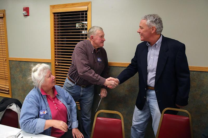 In this Jan. 24, 2014 photo, current GOP U.S. Senate primary candidate Ken Buck shakes hands with supporter Dale Gustafson, chairman of the Colorado Conservative Union, as Gustafson's wife Donna sits at left, during a campaign dinner event at Johnson's Corner, a truck stop and diner in Johnstown, Colo. Buck narrowly lost a 2010 Senate bid after being hammered for statements that angered some women and gays. Now his candidacy will be a test of whether a tea party favorite can do better in 2014. (AP Photo/Brennan Linsley)