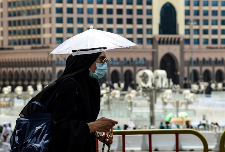 A pilgrim wears an umbrella hat to protect herself against the sun on the eve of the hajj