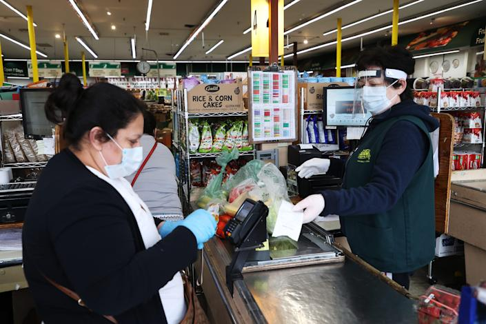 A shopper and cashier both wear masks, gloves and the cashier also has on a plastic visor at the checkout station Pat's Farms grocery store on March 31, 2020 in Merrick, New York.