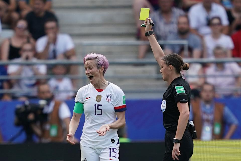 Hungarian referee Katalin Kulcsar (R) shows a yellow card to United States' forward Megan Rapinoe during the France 2019 Women's World Cup round of sixteen football match between Spain and USA, on June 24, 2019, at the Auguste-Delaune stadium in Reims, northern France. (Photo by Lionel BONAVENTURE / AFP)        (Photo credit should read LIONEL BONAVENTURE/AFP/Getty Images)
