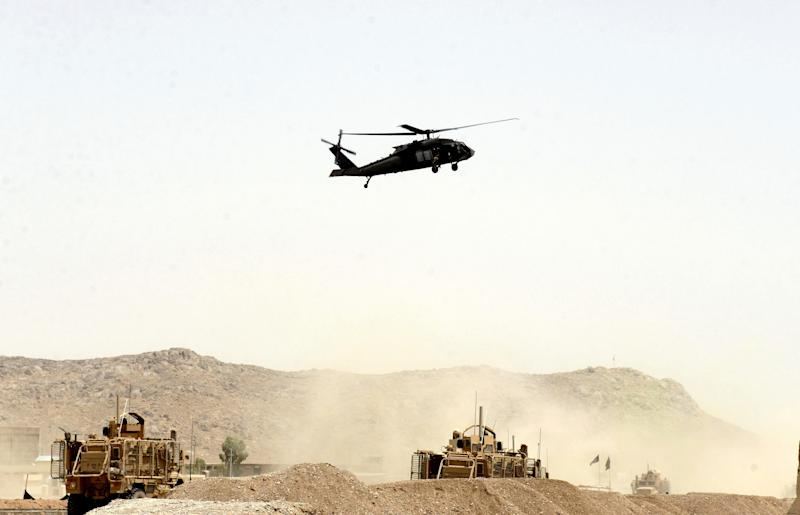 """In this Wednesday, Aug. 2, 2017 file photo, A US military helicopter flies over the site of a suicide bomb that struck a NATO convoy in Kandahar south of Kabul, Afghanistan. In an """"open letter"""" to U.S. President Donald Trump, Afghanistan's Taliban on Tuesday reiterated their call for a withdrawal of troops to end the protracted war."""