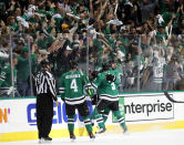 Fans cheer and linesman Mark Shewchyk (92) Dallas Stars' Miro Heiskanen (4), John Klingberg (3) and Mats Zuccarello, center rear, celebrate a goal by Zuccarello in the second period of Game 3 against the Nashville Predators in an NHL hockey first-round playoff series in Dallas, Monday, April 15, 2019. (AP Photo/Tony Gutierrez)