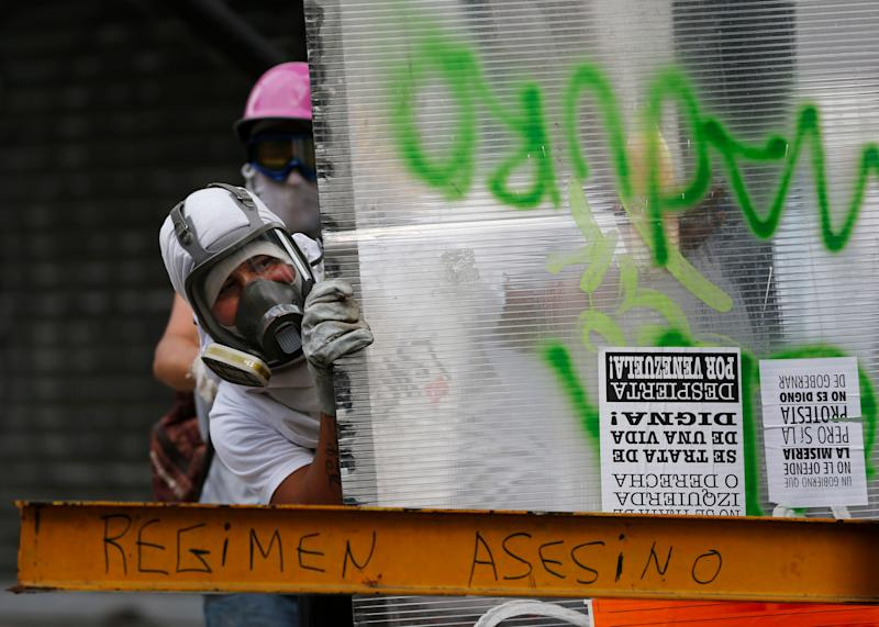 Masked anti-government demonstrators take cover from tear gas fired by Bolivarian National Police using a plastic sheet at a barricade in Caracas, Venezuela, Tuesday, April 1, 2014. Calling them guarimbas, which Venezuelans associate with home base in a child's game of hide-and-seek, President Nicolas Maduro has repeatedly cited the barricades as evidence that his opponents aren't fit to govern. (AP Photo/Fernando Llano)