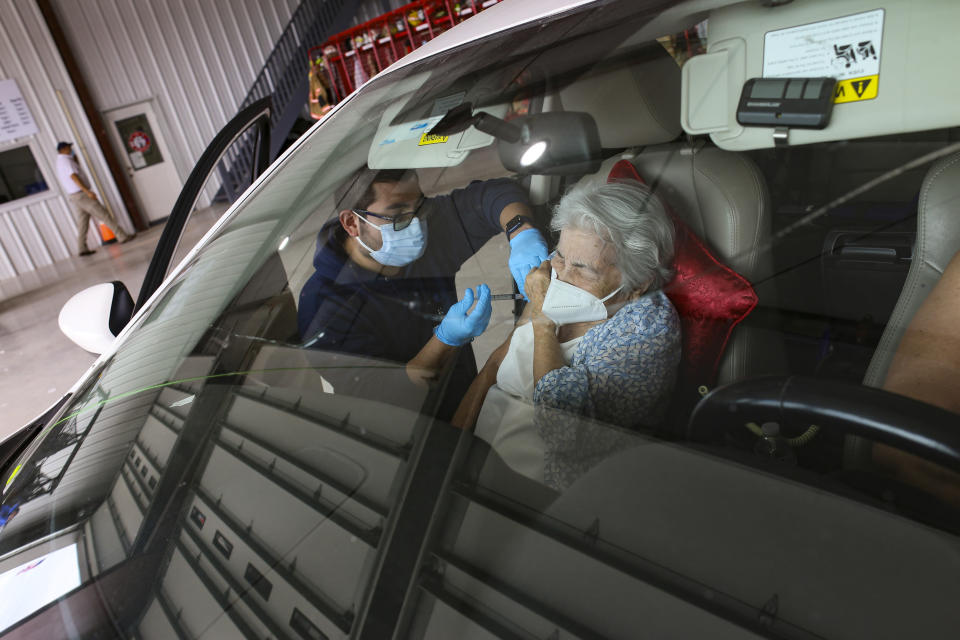 Medical Assistant Oscar Rojas leans in to administer the injection of the Moderna COVID-19 vaccine as 90-year-old Francisca Solis tightly shuts her eyes at the Los Fresnos Fire Station & EMS in Los Fresnos, Texas. Friday, Jan. 29, 2021, .(Denise Cathey/The Brownsville Herald via AP)