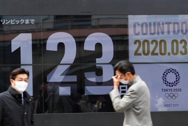 Passersby, wearing face masks due to the outbreak of the coronavirus disease (COVID-19), walk past a screen counting down the days to the Tokyo 2020 Olympic Games in Tokyo