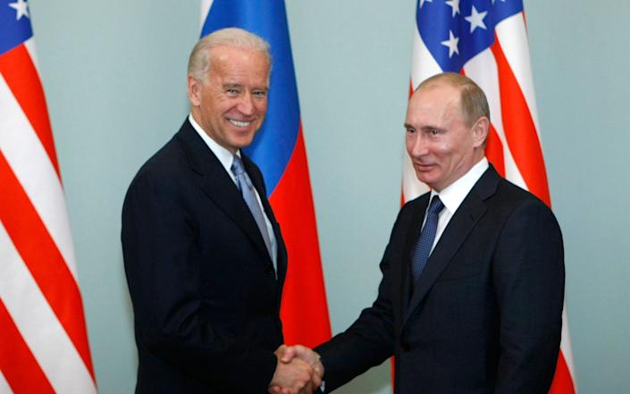 Joe Biden with Vladimir Putin in 2011. US intelligence officials said Russia was trying to prevent Mr Biden's election victory - AP
