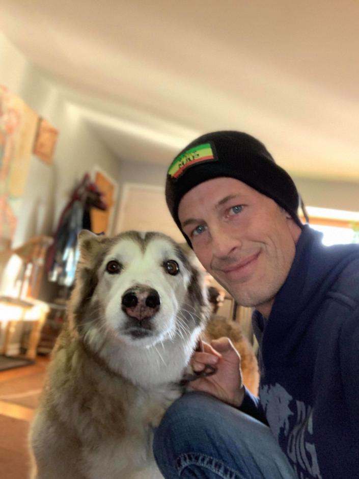 Ryan Arens poses with his malamute white shepherd mix named Hara.