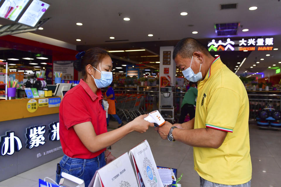 In this photo released by Xinhua News Agency, a resident goes through health screening to enter a supermarket in Ruili, southwestern China's Yunnan Province, on April 1, 2021. COVID-19 cases in the southwestern Chinese city of Ruili bordering on Myanmar have now topped 100 on Monday, April 5, 2021. That comes as authorities have launched an aggressive campaign to vaccinate all 300,000 residents of the city, whose outbreak is something of an anomaly in a country that has all-but eliminated local transmission of the virus.(Chen Xinbo/Xinhua via AP)
